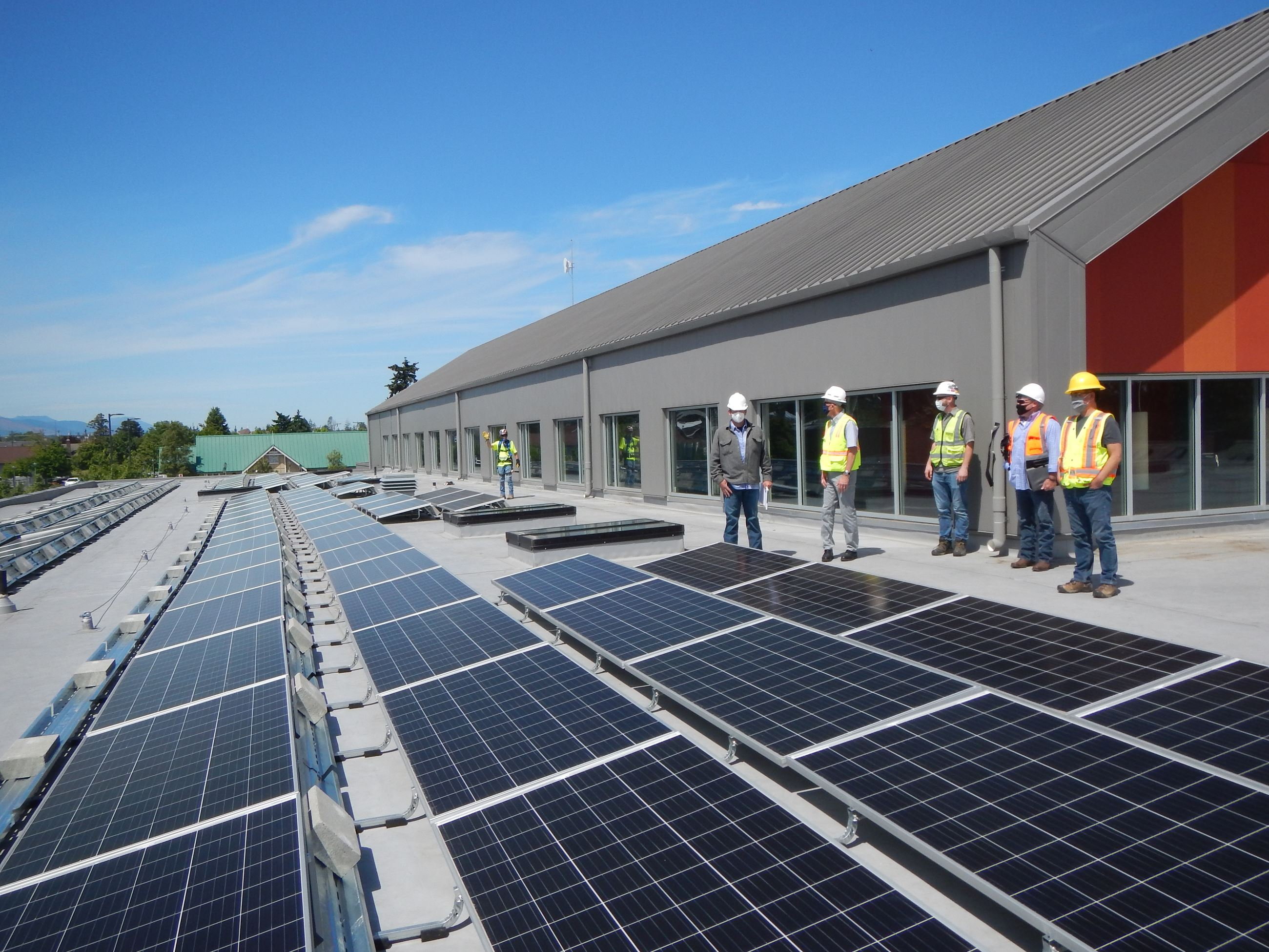Roof view with panels and staff on commissioning tour, May 2020