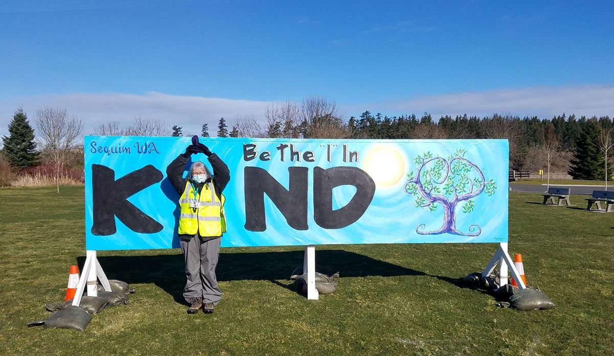 Volunteer in front of the Be the I in Kind sign